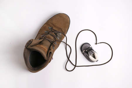 Photo for Two shoes, one big, one small, with a heart - Royalty Free Image