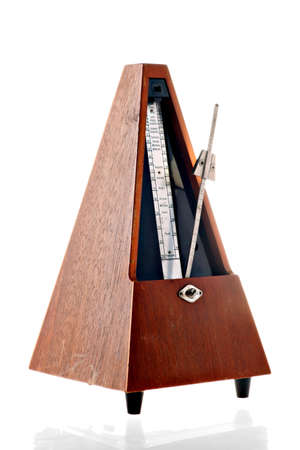 Vertical shot of a vintage metronome isolated on white