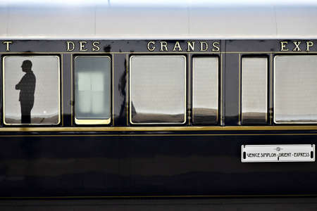Bucharest, Romania - September 3, 2012: A man is reflected in a window of the Orient Express train, shortly after arriving in Bucharest. The Venice Simplon-Orient-Express, is a private luxury train service, known as the Orient Express.