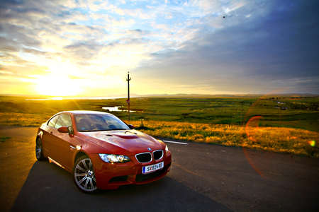Foto de Bucharest, Romania - July 3, 2013: A BMW M3 car drives through a beautiful scenery, at sunset. The BMW M3 is a high-performance version of the BMW 3-Series, developed by BMW's motorsport division, BMW M. - Imagen libre de derechos