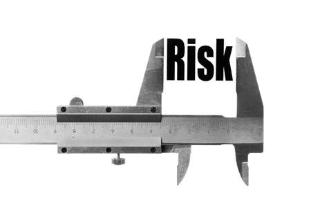 Close up shot of a caliper measuring the word Risk.