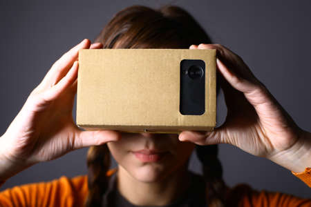 Color shot of a young woman looking through a cardboard, a device with which one can experience virtual reality on a mobile phone.