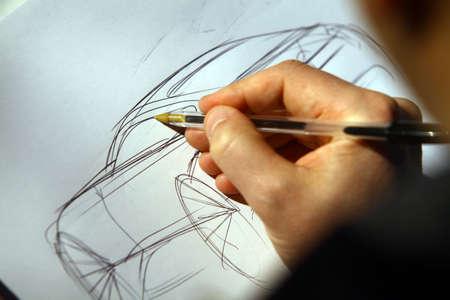 Foto de Close-up shot of a person's hand sketching a concept car. - Imagen libre de derechos