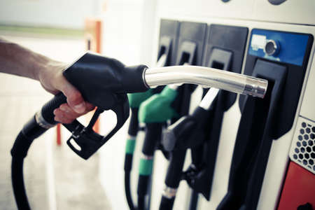 Photo for Detail of a hand holding a fuel pump at a station - Royalty Free Image