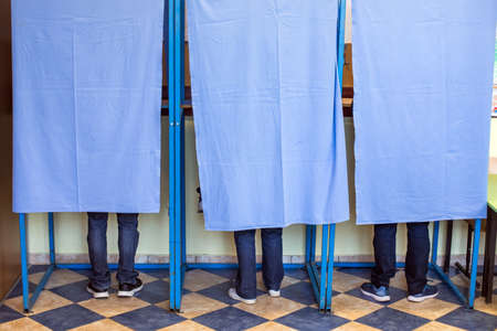 Color image of unidentifiable persons voting in booths at a polling station, during elections.