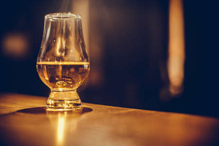 Photo for Color close up shot of a Glencairn whisky glass on a wooden table, with shallow depth of field. - Royalty Free Image