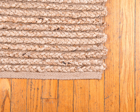 Jute pile hand woven beige area rug on old hardwood floor