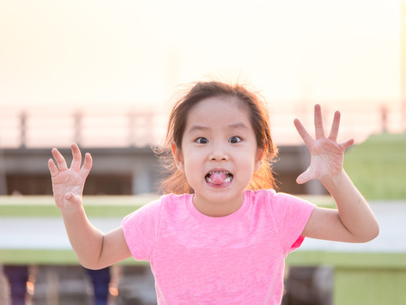Foto de Young cute cheeky girl , holding hands up with five fingers wearing pink t shirt,sticking out her tongue for funny face - Imagen libre de derechos