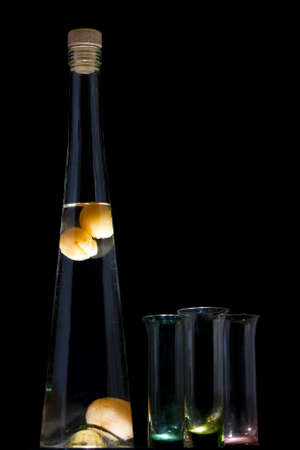 Hungarian apricot brandy or palinka with shot glasses against a black background