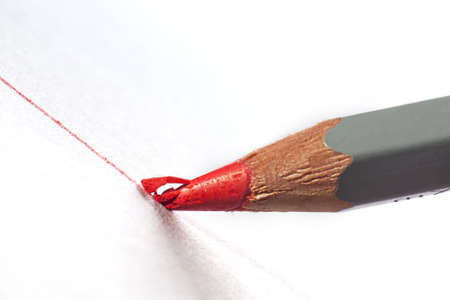 Pencil with red lead smashing whilst drawing a line in extreme close up