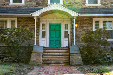 Photo pour A Teal Front Door on a Suburban Home With a Brick Path Leading Up to It - image libre de droit