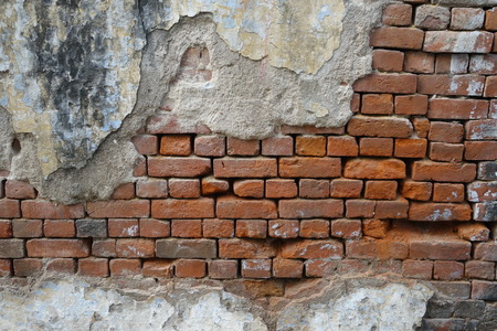 Old brick wall partially damaged in India
