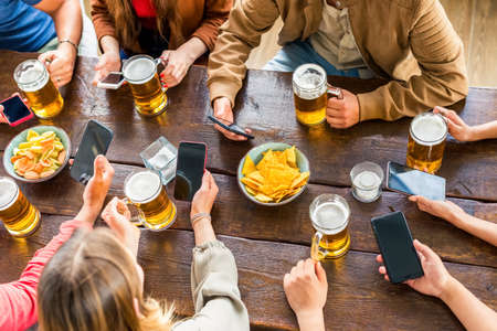 Foto de Multiracial group of friends enjoying a beer in a bar restaurant.Young people hands holding a beer and smartphone cheering.Friendship and youth life.tech, joy, togetherness concept.Up view with no faces - Imagen libre de derechos