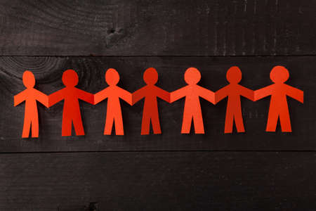 Group of paper doll holding hands. Teamwork concept papercraft. Orange dolls on black wooden background