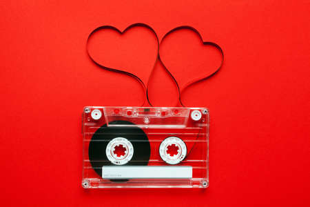 Vintage audio cassette with loose tape shaping two hearts on red background