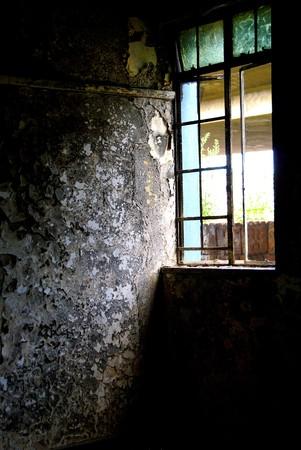 Broken window with paint peeling off the walls