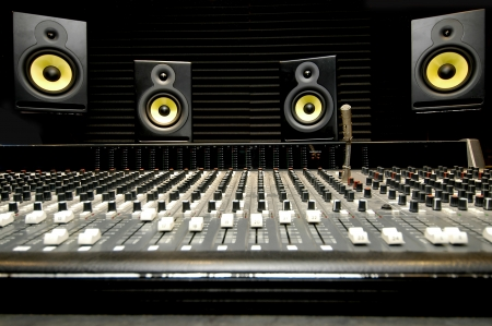 Low angle shot of a mixing desk with yellow and black speakers
