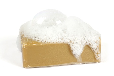 Organic soap with soap suds on top on a white background