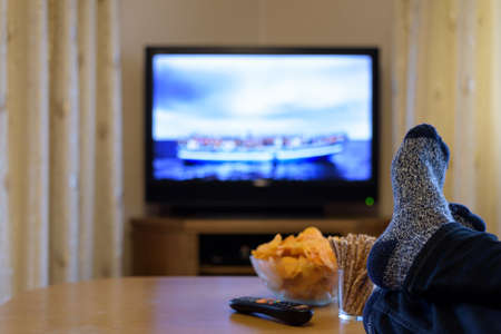 Photo pour TV, television watching (boat with people) with feet on table eating snacks - image libre de droit