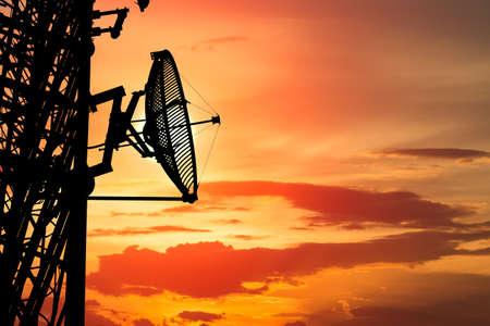 silhouette satellite communication tower poles on sunset