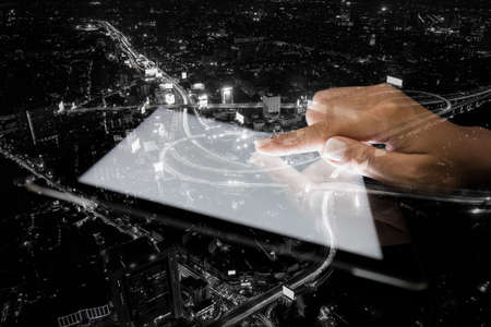 Photo pour double exposure hand using tablet and city on night background - image libre de droit