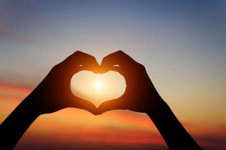 Photo for silhouette hand gesture feeling love during sunset - Royalty Free Image