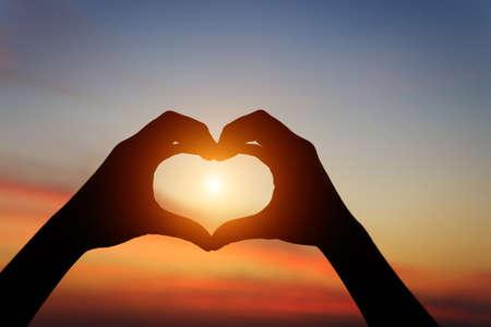 Photo pour silhouette hand gesture feeling love during sunset - image libre de droit