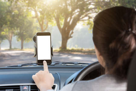 Photo pour woman use phone mount to glass in car on rural road - image libre de droit