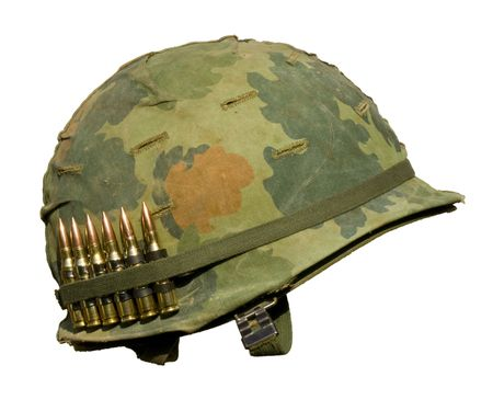 Photo for A US military helmet with an M1 Mitchell pattern camouflage cover from the Vietnam war, and six rounds of 7.62mm ammunition. - Royalty Free Image