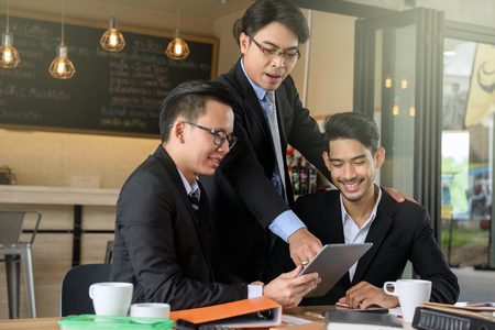 Photo pour business man boss coaching two happy young businessman by using digital tablet to show project plan and update progress using 4g technology. Fintech business and working from home concept. - image libre de droit