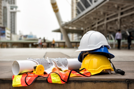 Foto de Safety helmet hats, blueprint paper project, measure tape, gloves, and worker dress on concrete floor at modern city with blurred people. Engineer and construction equipment with copy space for text. - Imagen libre de derechos