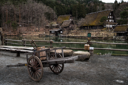 Photo for Old wooden handbarrow in front of sloped-roof and thatched-roof houses at Hida Folk Village, Takayama, Japan. Here is famous of similarity preserved village as Shirakawago. - Royalty Free Image