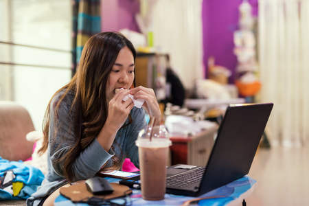 Photo pour Busy Asian female businesswoman eating sandwich and watching sale order at laptop computer and smartphone. Work from home for online business owner. - image libre de droit