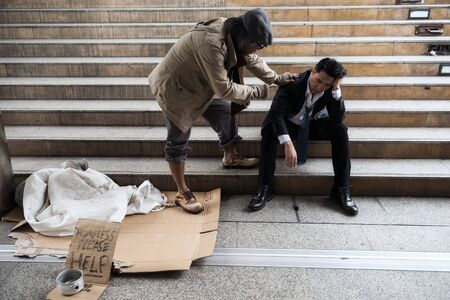 Photo for Old homeless beggar man cheer up sad businessman in city. Unemployed business man get fired due to covid-19 or coronavirus. Leave without pay, quarantine, work from home, global pandemic disease. - Royalty Free Image