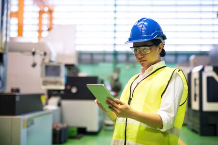 Photo pour Waist up female worker with hardhat and protection glasses use corporate applciation to check automate robot machines in factory. Manufacture industry with technology. social distancing during covid-19. - image libre de droit