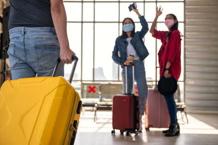 Photo pour man pull luggage while his friends with face mask waving hand to say hi at airport departure terminal.Travel with new normal to prevent covid-19 pandemic disease. - image libre de droit