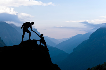 Teamwork couple helping hand of assistance trust in mountains sunset silhouette. Team of climbers man and woman hiker help each other on top of a mountain climbing assistance beautiful sunset landscape in Himalayas Nepal