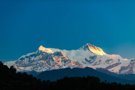Mountain inspirational beautiful sunset landscape in Himalaya Mountains. IV7525m Himalayas Annapurna and Annapurna II7937m peaks over blue sky. Looking at mountains landscape view from Pokhara city, Nepal.