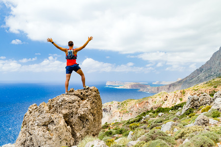 Success achievement running or hiking accomplishment or business concept, man celebrating with arms up raised outstretched trekking climbing trail running outdoors. Motivation and inspiration looking at beautiful landscape view.