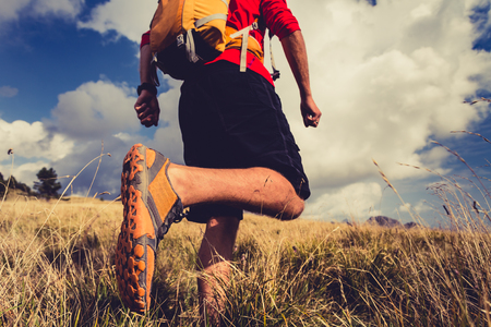 Man hiking or trail runner walking in mountain landscape inspirational. Fitness and healthy lifestyle hiker or trekker walk on dry grass, fall autumn nature. Travel in Italy, Europe. Selective focus on a sports shoe.