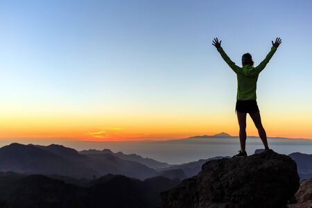 Woman successful hiking or climbing in mountains, motivation and inspiration in beautiful sunset landscape. Female hiker with arms up outstretched on mountain top looking at view.