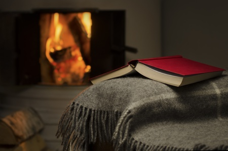 Peaceful and warm image of open book resting on a arm rest of a couch  Warm fireplace on background