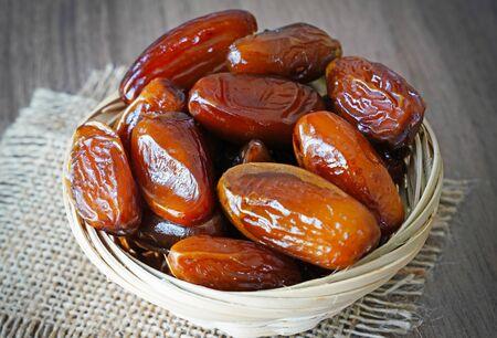 Photo pour Fresh fruit dates in a basket bowl on a piece of sackcloth on walnut wooden table - image libre de droit