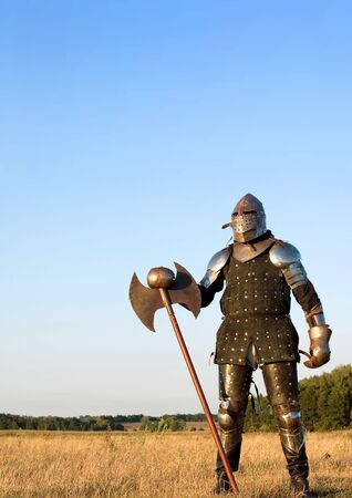 Photo for Medieval knight in the field with an axe - Royalty Free Image