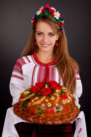 Young woman in ukrainian clothes, with garland and round loaf on black background