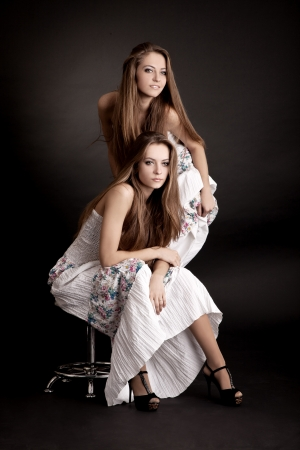 Two beautiful girls twins, isolated on the grey background