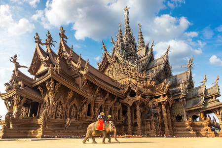 Foto de Tourists ride elephant around the Sanctuary of Truth in Pattaya, Thailand in a summer day - Imagen libre de derechos