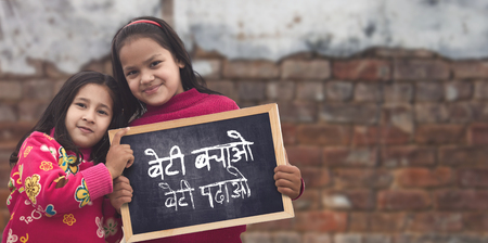 Photo for Adorable little 6-8 years old and 8-10 years old Asian girls smiling, holding beti bachao beti padhao chalkboard. Save and educate Daughter concept - Royalty Free Image