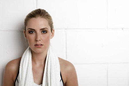 Beautiful blond woman standing against a wall in a gym with a towel around her neck.