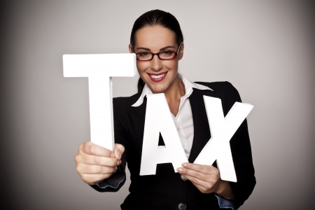 A businesswoman holding letters to spell out tax as a pay your tax concept